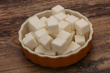 Refined white granulated sugar cubs in the bowl