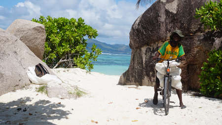 Seychelles. La Digue. 19.10.2015 Local citizen in La Digue Island dressed up in brazil t-shirt on the bike. Redactioneel