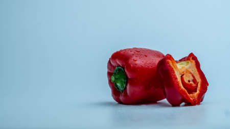 Red bell pepper with chopped portion on blue gradient background on the right side of the frame Stockfoto