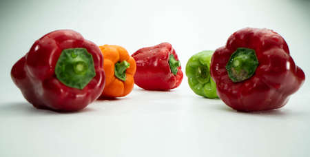 Four red green and orange sweet peppers isolated on white background. Close-up shot