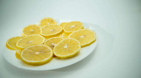 Many pieces of fresh lemon lie on hte white glass place with white background
