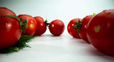 Many red tomatoes and parsley on the white isolated background. Low angle macro shot