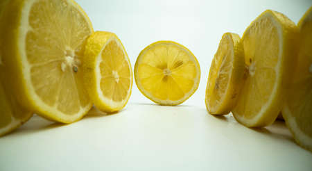 Slices of fresh lemons on the table with white background, Lemon