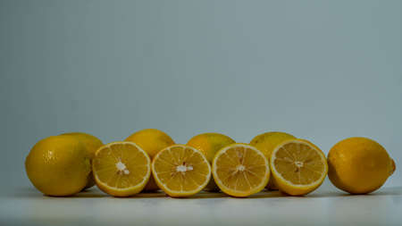 Six fresh yellow lemons on the white background. Cut lemon.