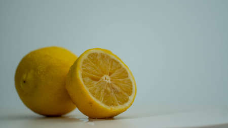 Two fresh lemons on the white background. Whole lemon and half. Stockfoto
