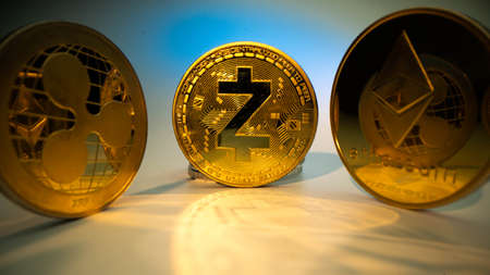 Crypto currency ZCASH ZEC Etherium ETH, Ripple XRP. Golden coin with white background Use for logos, print products, page and web decor or other design. Macro angle.