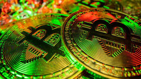 2 most popular crypto coins in the world. Bitcoin in green and red light with reflection
