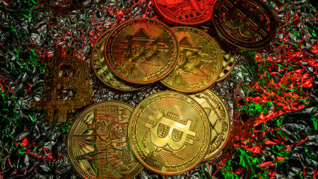 Many crypto coins on the table with nice reflections. Green and red light. Top view