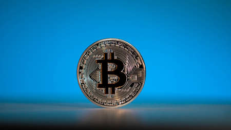 Silver coin of main cryptocoin in the world. Bitcoin with blue background Stockfoto