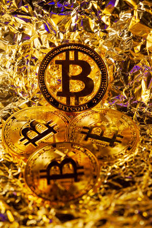 4 gold Bitcoin with golden reflect background. Great close-up shot. Stockfoto - 147146313