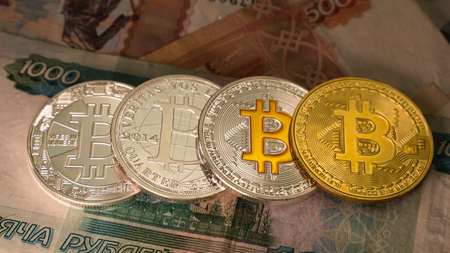 Four different colours cryptocoins Bitcoin on the table with russian cyrrency Stockfoto