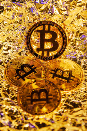 4 gold Bitcoin with golden reflect background. Great close-up shot. Archivio Fotografico - 147147696