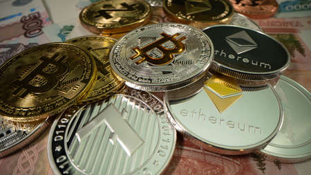 Many crypto coins Bitcoin, Litecoin. Etherium, Zcash, Ripple, Monero on russian money. Many bills. Macro shot. Stockfoto