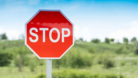 Red Stop Traffic Sign on Blue Sky Background and green field