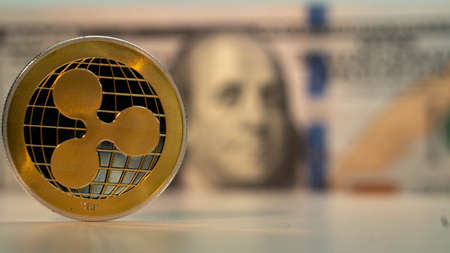 Golden crypto coin Ripple XRP on the foreground and hundred dollar USA on the background Stockfoto