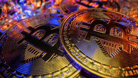 Two gold cryptocoins Bitcoin on the table with gold and blue fantastic reflections. Macro shot from Laowa 24mm.
