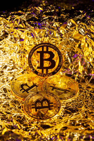 Gold Bitcoin Cryptocurrency in the centre surrounded by another coins with golden background. Halving. Trading. Reflection. Mining. Archivio Fotografico - 148798992