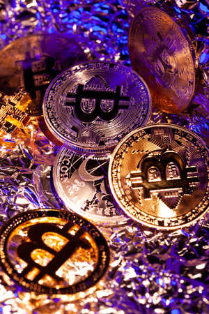 Many gold coins Bitcoin with blue and yellow light. Many nice reflections. Close-up shot Archivio Fotografico - 149828873