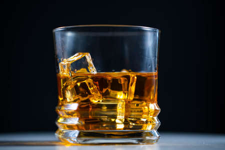 Whiskey poured into a glass with ice, in slow motion, macro shooting, on a wooden table and dark background. Concept: alcohol, spirits, for a good evening, alcohol harms health