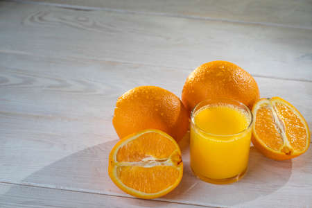 Orange juce and oranges are standing on the white background