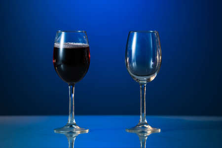 Red wine glass and white wine glass isolated on a blue background Archivio Fotografico