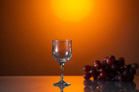 Empty Glass for white wine over white grapes. Sun breaks through the branches of the vineyard and illuminates shaking glass of white wine. Waving white wine