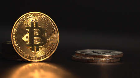 Golden Bitcoin BTC with reflection on the glass. Many oher crypto coins appea one after another in frame Black background.
