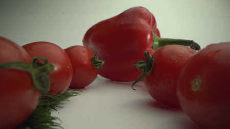 Freshly plucked vegetables. Tomatoes and bell peppers on a white table. Summer food. Before cooking. Macro