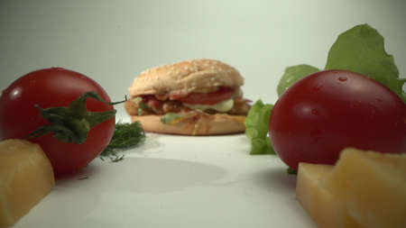 The camera moves past tomatoes, cheese and herbs to a delicious hamburger.