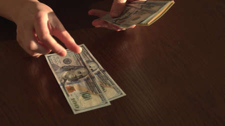The girl holds a pack of American dollars in her hands and puts them on the table one banknote to count the number