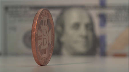 Cripto coin with Bitcoin symbol isolated on foreground. Coin rotate. 100 US dollars is ont the background with nice blur. Virtual money of the future. Close up shot. Archivio Fotografico