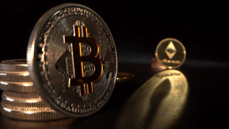 Silver and bronze crypto coin BITCOIN BTC and Etherium with golden reflection. Black background. Focus moves from one coin to another.