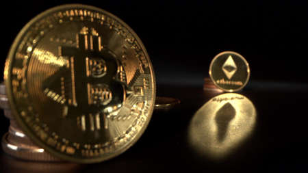Gold Bitcoin BTC and gold Etherium with black background with reflection on the surface. Trading. Halving. Archivio Fotografico
