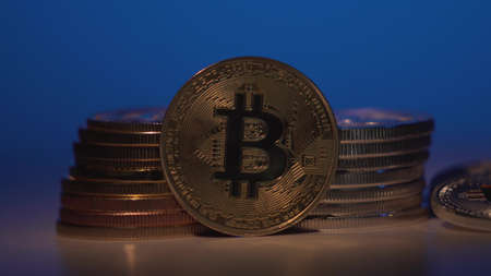 Bitcoin. Crypto currency Gold Bitcoin, BTC, Bit Coin. Macro shot of Bitcoin coins rotated with another gold coins. Gradient blue background. Blockchain technology, bitcoin mining concept. Archivio Fotografico