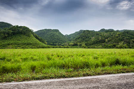 urban jungle: Green fields and mountains with moody sky before rain Stock Photo