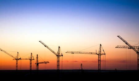 condo construction: Cranes on a construction site against a sunset sky