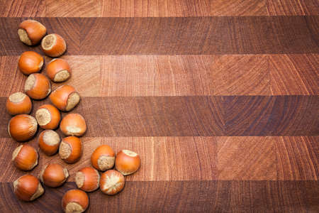 disposed: Wooden  surface  with hazelnuts and copy space. Handful of hazelnuts disposed from left side. Right side can be used for text