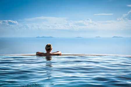 pool water: Woman relaxing in infinity swimming pool in luxury resort Stock Photo