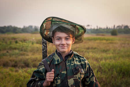 bullet camera: Young smiling boy with hunting shotgun standing at green field during sunset Stock Photo