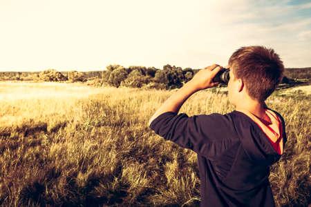 El muchacho joven con los prismáticos en un campo de trigo que mira en la distancia. concepto para el futuro, el descubrimiento, la exploración y la educación