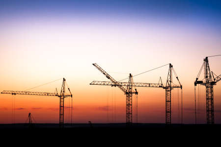construction machinery: construction site with cranes against a sunset sky