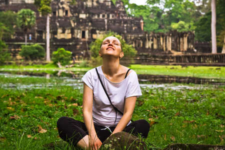 ancient yoga: Young woman relax outdoors on grass in lotus pose among ancient ruins during vacation Stock Photo