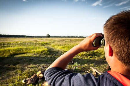 using senses: Young boy with binoculars in a wheat field looking into the distance. concept for future, discovery, exploring and education Stock Photo