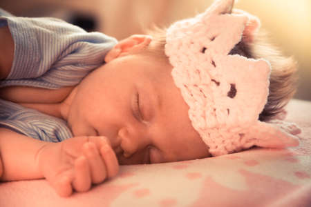 bebes ni�as: A portrait of sweet baby girl with crown sleeping on soft pink blanket with back light