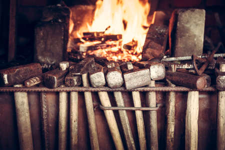 Blacksmith shop with hammers and burning furnace on background Stock Photo