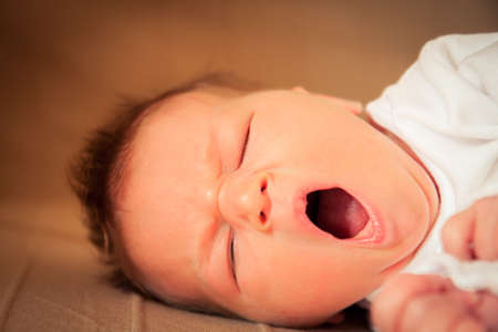 newborn yawning baby with closed eyes taking a nap