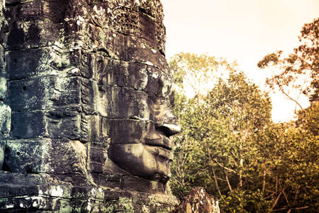 social history: Face of Bayon Temple with falling sunlight, Angkor Thom, Angkor Wat, Cambodia, Southeast Asia.