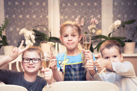 children party: children toasting with juice in festive glass at children party
