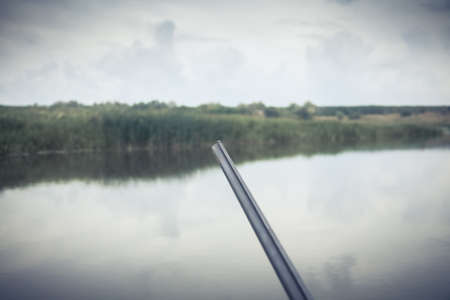 duck hunting: Gun barrel ready to shot during duck hunting season on river bank in overcast day Stock Photo