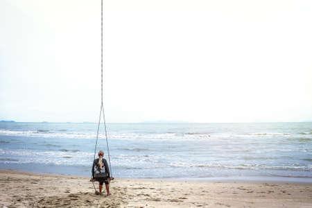mujer mirando el horizonte: Sola mujer sola movimientos de balanceo y mirando en la distancia sobre el horizonte en una playa tropical con espacio de copia. Una brillante luz del sol ilumina el mar y el cielo